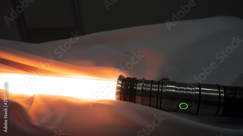Photo Activated lightsaber resting on fabric