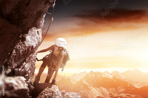 Frau an einem Klettersteig (Via Ferrata) bei Sonnenaufgang