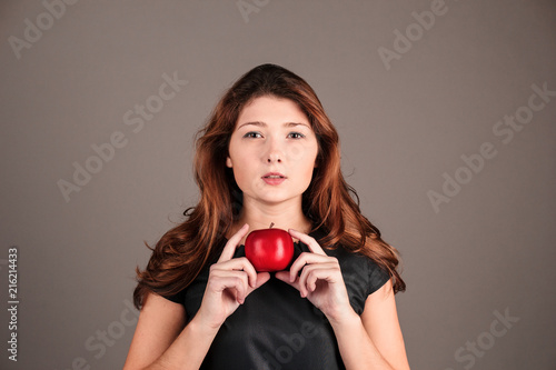 Láminas  Portrait of a fashionable elegant girl in a black dress with red apple on a dark background