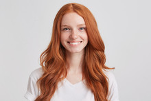 Closeup Of Cheerful Lovely Redhead Young Woman With Long Wavy Hair And Freckles Wears T Shirt Looks Confident And Feels Happy Isolated Over White Background Looks Directly In Camera