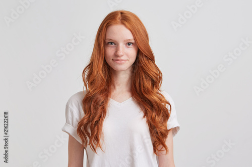 Fotografie, Obraz  Closeup of happy attractive young woman with long wavy red hair and freckles wea