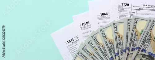 Canvastavla Tax forms lies near hundred dollar bills and blue pen on a light blue background