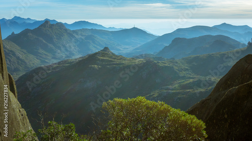 Foto op Aluminium Blauwe jeans Landscape among mountains in a naturally green setting with the sun shining at dusk
