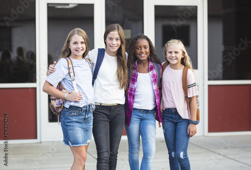 Photo Group of pre-adolescent school kids smiling while smiling together at school