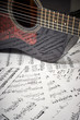 dark acoustic guitar on a background sheet notes, close-up