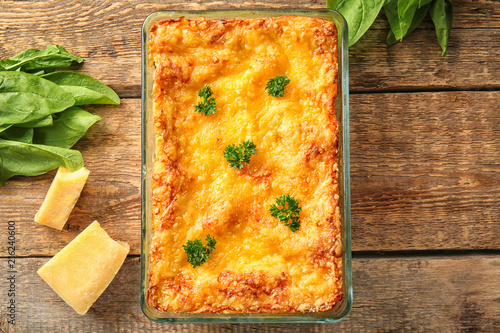 Delicious lasagna with spinach and Parmesan cheese on wooden background