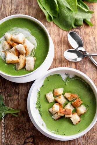 Fototapeta Bowls with delicious spinach soup on table obraz