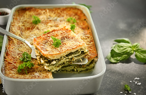 Spatula with piece of spinach lasagna over baking dish