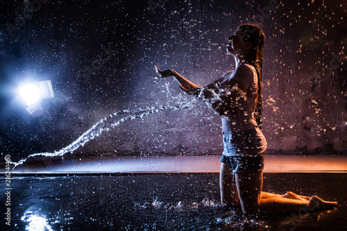 Girl with wet hair in the white shirt, water drops around and dark wall background illuminated by light