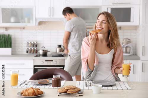 Beautiful young woman having breakfast while her beloved boyfriend cooking in kitchen