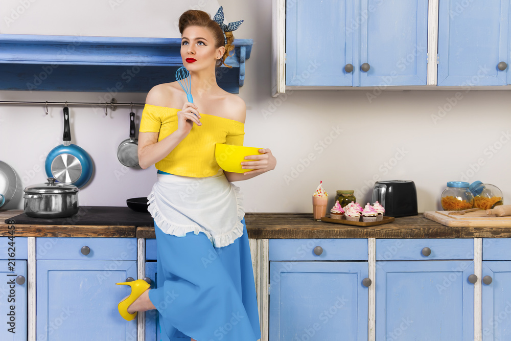Fototapeta Colorful retro / pin up girl woman female  / housewife wearing colorful top, skirt and white apron holding whipper and bowl in the kitchen with blue cabinets and utensils and cupcakes with milkshake.