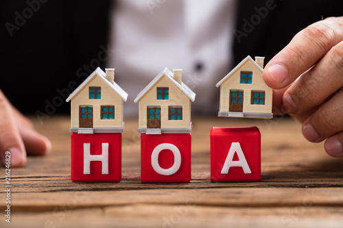 Photo Businessperson placing house model over HOA blocks
