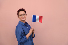 France Flag. Woman Holding French Flag. Nice Portrait Of Middle Aged Lady 40 50 Years Old With A National Flag Over Pink Wall Background. Learn French Language. Visit France Concept.