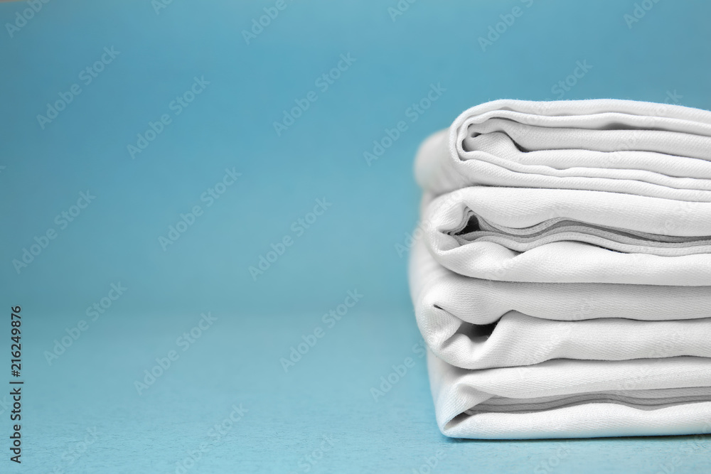 Fototapety, obrazy: Stack of clean bed sheets on color background