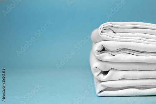 Valokuva  Stack of clean bed sheets on color background