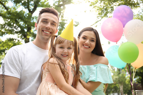 Fototapeta Cute little girl with her parents at birthday party outdoors obraz