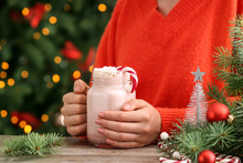Woman With Mason Jar Of Delicious Cocoa At Table Against Blurred Christmas Lights, Closeup