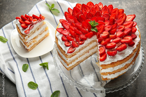 Stand and plate with delicious strawberry cake on table Poster Mural XXL