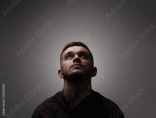 Facet portrait a man looking up. Dark lighting portrait bristle men in checkered shirt looks up with his head up on a dark gray background copy space Fotomurales