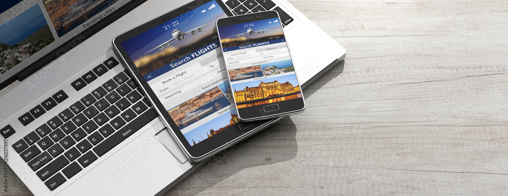 Fototapeta Smartphone and tablet on a computer keyboard, Search flights on the screens, wooden background, copy space. 3d illustration