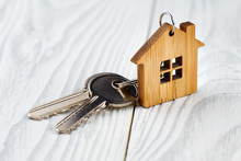 House Keys With House Shaped Keychain On Wooden Background