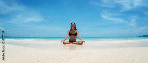 Yoga woman meditating at serene tropical beach, morning zen mediation