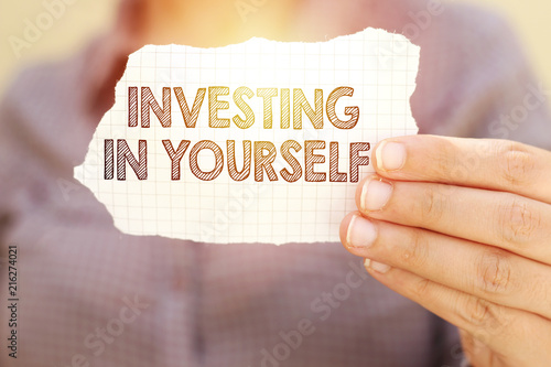 Fotografía  business woman holding tear paper with investing in yourself text