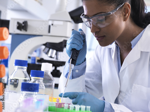 Genetic research, female scientist pipetting DNA or chemical sample into a eppendorf vial, analysis in the laboratory