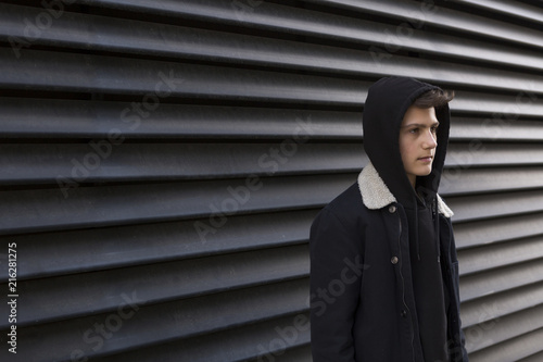 Serious teenage boy wearing hooded jacket standing in front of black background