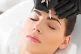Fototapeta Kuchnia - Young woman undergoing procedure of eyebrow permanent makeup in beauty salon