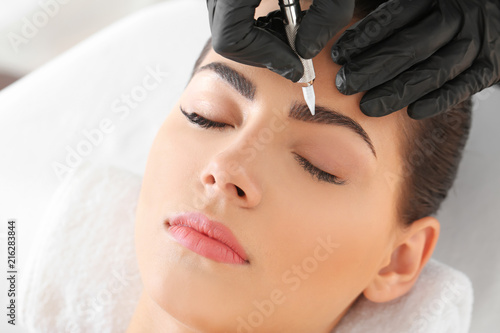Canvas-taulu Young woman undergoing procedure of eyebrow permanent makeup in beauty salon