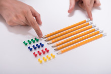 Person's Hand Arranging Pencils And Multi Colored Pushpins