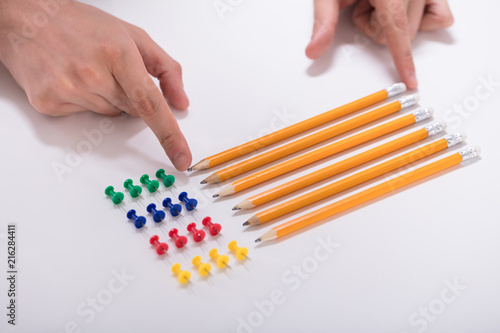 Fotografie, Tablou Person's Hand Arranging Pencils And Multi Colored Pushpins