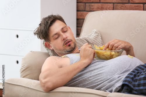 Fotografie, Obraz  Lazy man with bowl of chips sleeping on sofa at home
