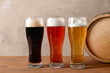 Glasses with different types of cold tasty beer on wooden table