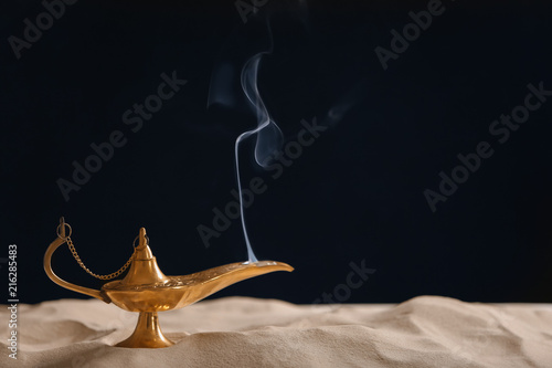 Aladdin lamp of wishes on sand against black background