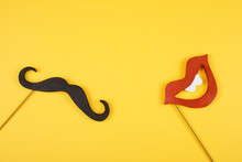 Moustache And A Red Mouth On Wooden Sticks Against A Bright Yellow Background (copy Space For Your Text)