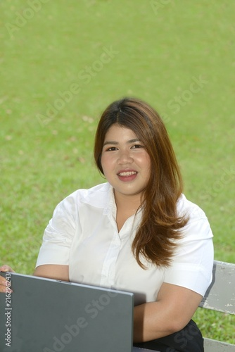 Portrait of pretty smiley face Asian fat woman pose working with laptop on a chair in the park Canvas Print