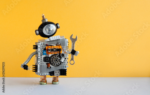 Photo  Hand wrench robot serviceman on yellow background
