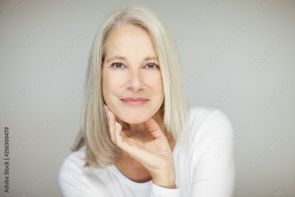 Fototapeta stunning beautiful and self confident best aged woman with grey hair smiling into camera, portrait with white background