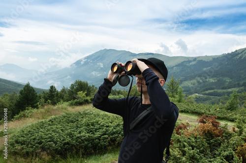 Junger wanderer mit fernglas schaut sich die berge an u2013 kaufen sie
