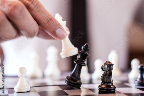 Obraz na plátne Hand of confident businessman use king chess piece white playing chess game to c