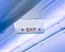 Vintage Tone Emergency Exit Sign With Red Arrow On Ceiling Of Airplane. Illuminated Evacuation Symbol Underneath The Overhead Compartments. Shining Signboard Show Escape Of Emergency, Urgency Concept