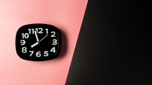 Black Clock On Pink And Black Background.