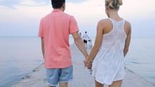 Young Couple Walking At Sea Pi...