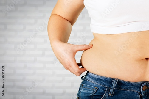 Slika na platnu Woman's hand holding excessive belly fat