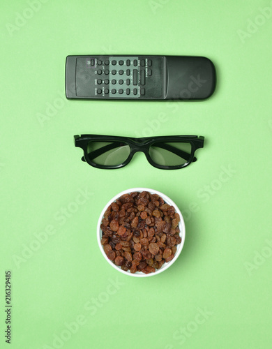 Valokuva  3d glasses, tv remote,  bowl with raisins on pink pastel background, top view
