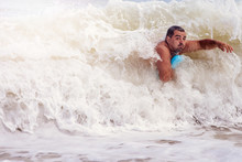 A Man Swims In The Raging Sea, It Covers A Huge Wave.
