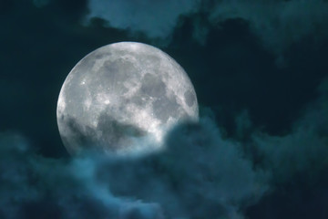 Halloween night sky with clouds and appearance of a full moon with craters close up
