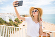 Pleasant girl in sunglasses and hat make kiss on camera while making selfie on sea background.